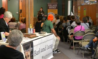 Answering questions at Village Books while Alice serves cake